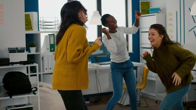 Mieszane wyścigowe szczęśliwe kobiety tańczą radośnie w biurze startupowej agencji kreatywnej