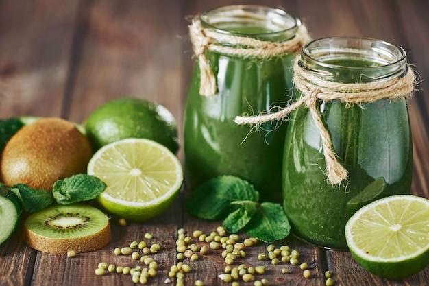 Mieszane zielone smoothie ze składnikami na kamiennej desce, drewniany stół selektywnej ostrości