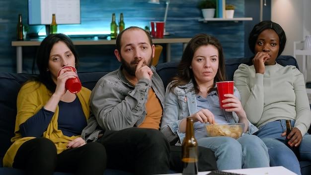 Mieszani przyjaciele relaksujący się na kanapie podczas oglądania filmu komediowego w telewizji, śmiejący się podczas imprezy domowej późno w nocy w salonie. grupa wielorasowych ludzi cieszących się wspólnym czasem