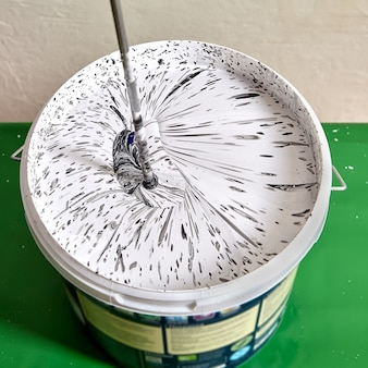 Mieszanie białej farby z czarnym pigmentem w celu uzyskania szarego koloru
