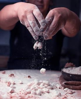 Mieszanie gotowych kawałków tureckiego manti z mąką.