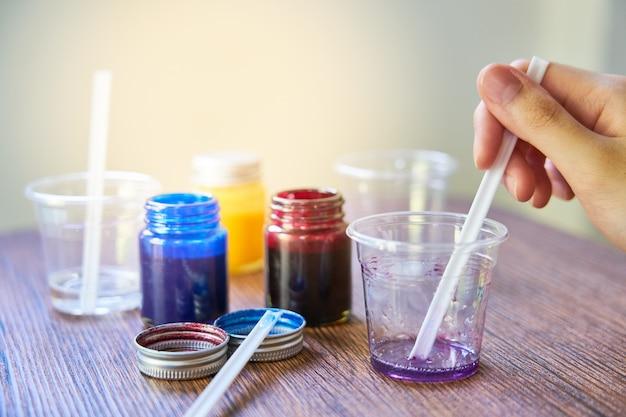 Mieszanie kolorowych chemikaliów z żywicy w plastikowym kubku, proces wytwarzania akcesoriów z żywicy