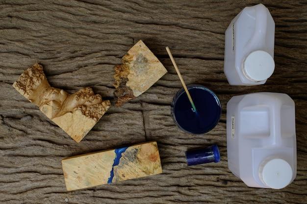 Mieszanie koloru niebieskiej żywicy epoksydowej w szklanym kubku do odlewania drewna burl na starym drewnianym stole w tle