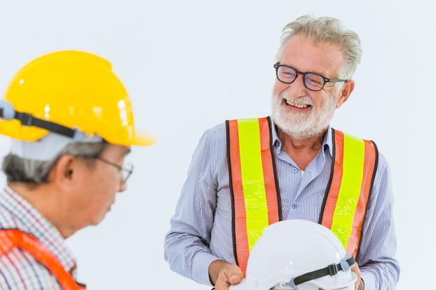 Mieszanka biegowy starszy inżyniera pracownik budowlany opowiada wpólnie szczęśliwego uśmiech pracuje z ciężkim kapeluszem