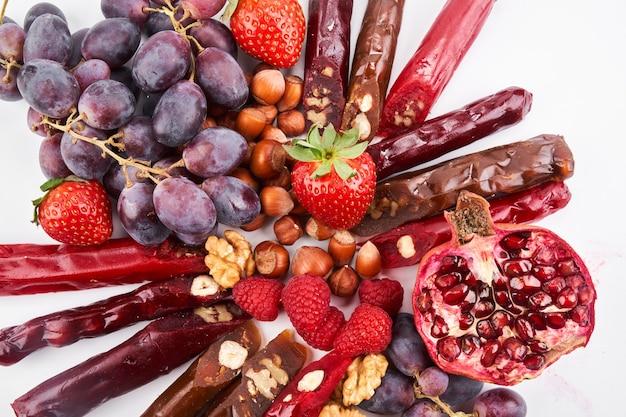 Mieszanka churchkhela, owoce, jagody i orzechy na białym stole, kaukaskie słodycze