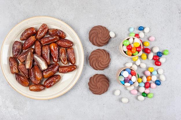 Mieszanka ciasteczek, daktyli i posypanych cukierków na marmurowej powierzchni.