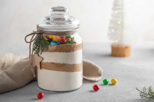 Mieszanka ciastek z kolorowymi cukierkami w szklanym słoiczku suche składniki do robienia świątecznych ciasteczek