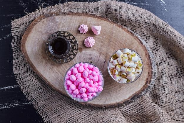 Mieszanka cukierków podawana ze szklanką herbaty.