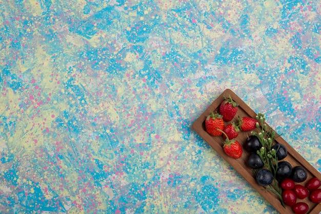 Mieszanka jagód na drewnianym talerzu izolowanym w rogu