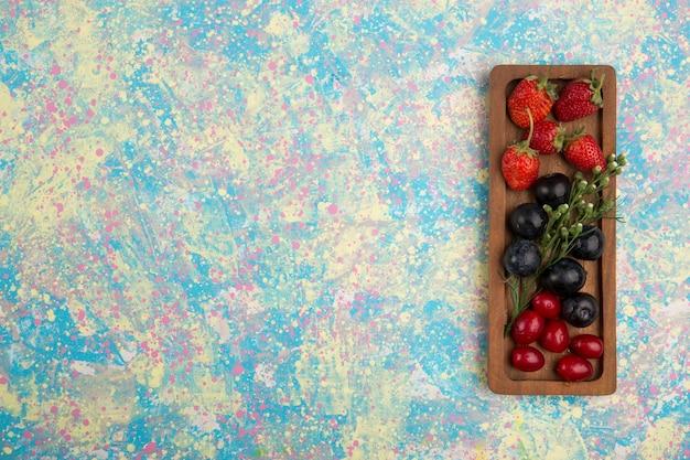 Mieszanka jagód na drewnianym talerzu na białym tle na niebieskim tle