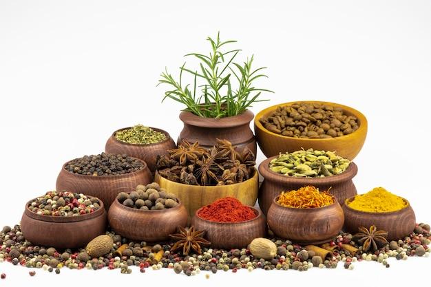 Mieszanka kolorowych aromatycznych i gorzkich papryczek rozsypanych wśród przypraw w drewnianej misce na białym tle.