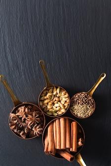 Mieszanka konceptu żywnościowego przypraw masala, cynamonu, kopru włoskiego, anyżu gwiazdkowatego, nasion kolendry i strąków cynamonu w miedzianym kubku na czarnej tablicy łupkowej