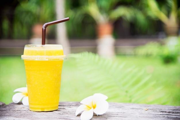 Mieszanka lodu z mango i pomarańczy w zielonym ogrodzie