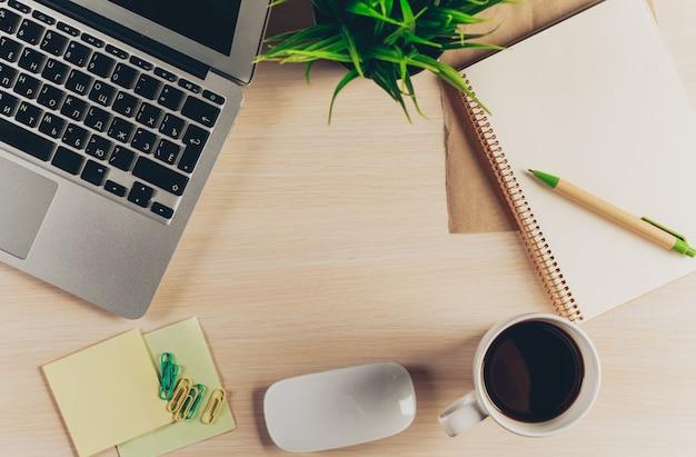 Mieszanka materiały biurowe i gadżety na drewnianym stołowym tle.