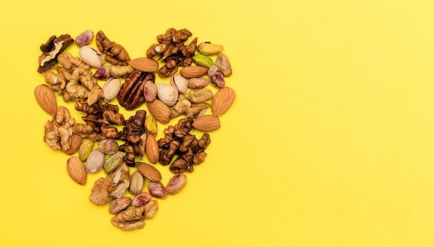 Mieszanka orzecha włoskiego, pistacji, pekanu, migdałów ułożona jest w formie serca. pojęcie zdrowej żywności. mieszkanie ketogeniczne.