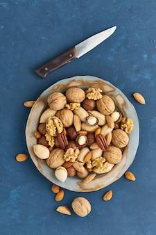 Mieszanka orzechów na talerzu - orzech, migdały, orzechy pekan, makadamia. zdrowe wegańskie jedzenie.