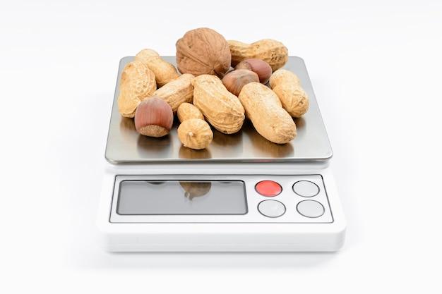 Mieszanka orzechów na wadze elektronicznej z białym tłem. koncepcja diety i odchudzania.