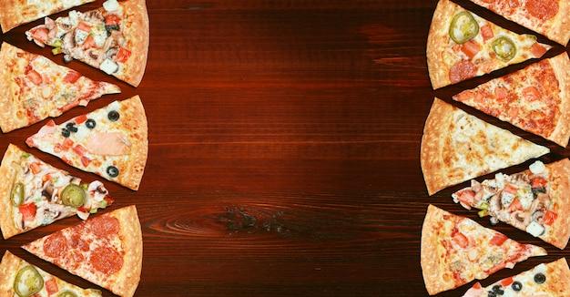 Mieszanka ośmiu różnych pizzy na drewnianym stole menu koncepcji wyboru i różnorodności