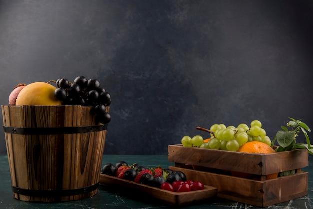 Mieszanka owoców i jagód w drewnianych pojemnikach na niebieskiej przestrzeni