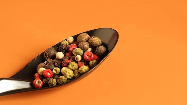 Mieszanka papryki ostrej, czerwonej, czarnej, białej i zielonej w czarnej łyżce. na białym tle na brązowym tle.