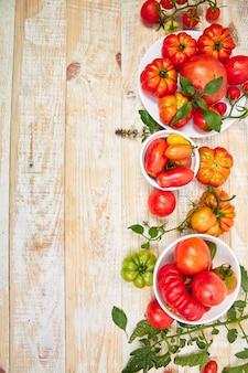 Mieszanka pomidorów w tle. piękne soczyste organiczne czerwone pomidory