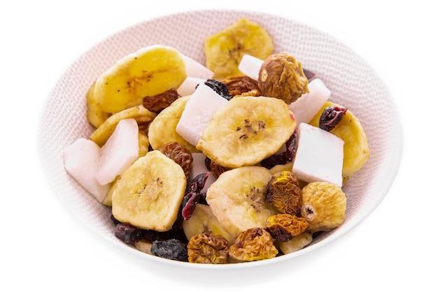 Mieszanka posiekanych suszonych owoców i orzechów jagodowych na białym talerzu na białym tle pojedyncze przedmioty i produkty