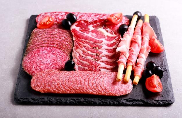 Mieszanka produktów mięsnych na czarnej tablicy