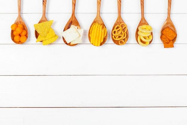 Mieszanka przekąsek: precle, krakersy, frytki i nachos na białym tle drewnianych