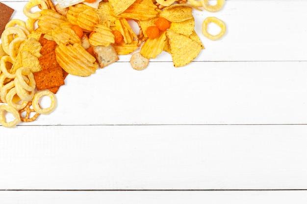 Mieszanka przekąsek: precle, krakersy, frytki i nachos na tle stołu