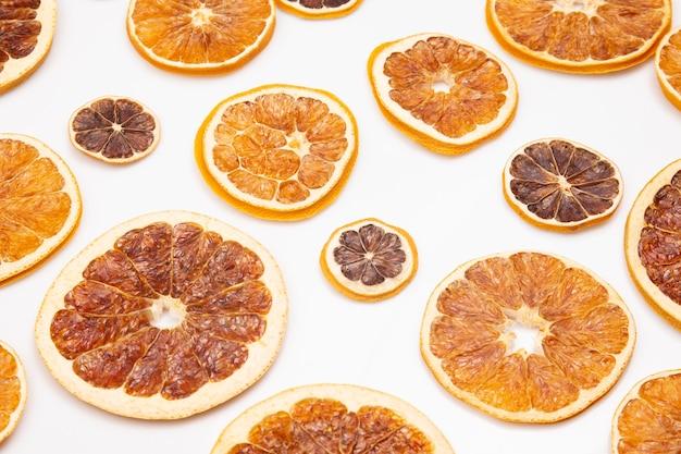Mieszanka różnych kawałków suszonych owoców cytrusowych na białym tle