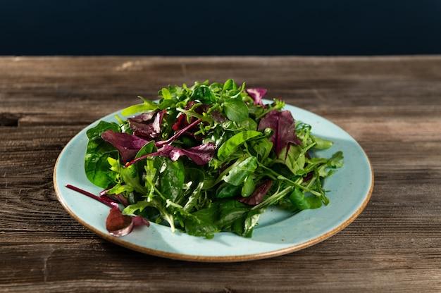 Mieszanka sałat ze świeżych ziół w talerzu na drewnianym stole
