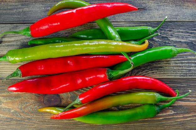 Mieszanka sterty surowych czerwonych i zielonych papryczek chili lub capsicum frutescens, na ciemnym drewnianym stole.