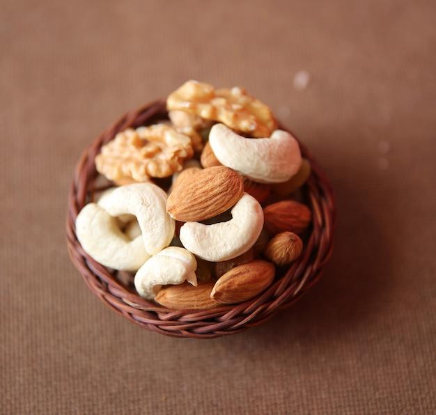 Mieszanka suchych orzechów i owoców z bliska z drewnianym koszem