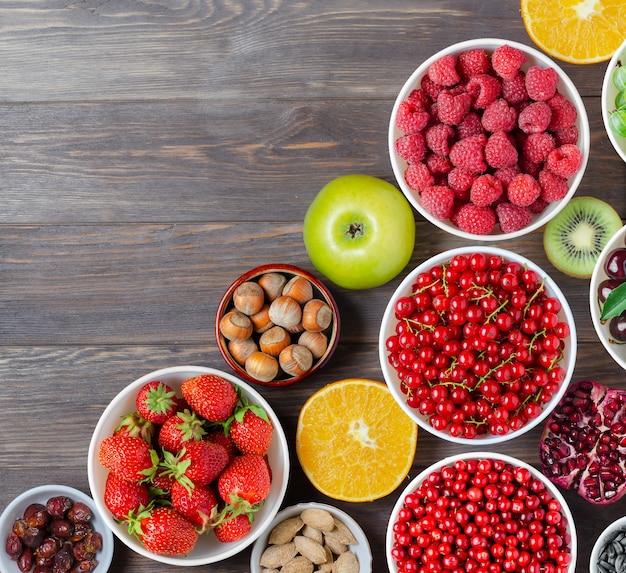 Mieszanka świeżych jagód, orzechów i owoców na drewnianym tle
