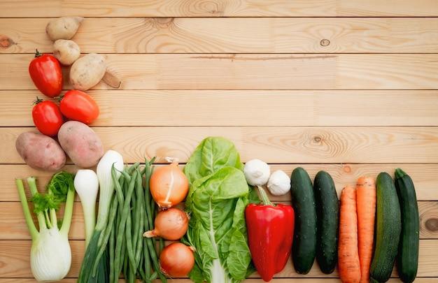 Mieszanka świeżych warzyw na drewnianym stole. zdrowa i dietetyczna żywność. wegańska i wegetariańska. kolorowe i bogate w witaminy