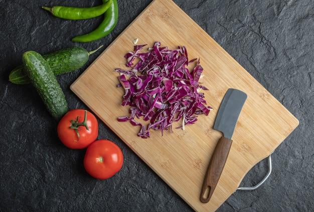 Mieszanka warzyw. siekana kapusta, ogórek, pomidor i papryka na czarnym tle