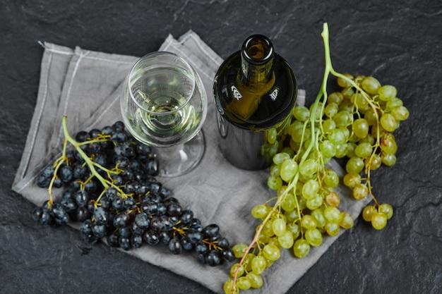 Mieszanka winogron, kieliszek wina i butelka z szarym obrusem na ciemnej powierzchni