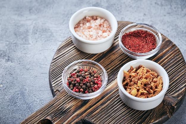 Mieszanka ziaren czerwonego i czarnego pieprzu, gruboziarnista różowa sól himalajska, suszone pomidory i suszona cebula w małych miseczkach