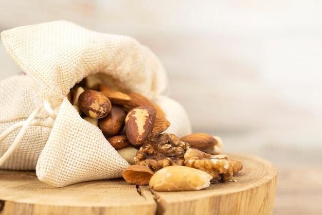 Mieszankę orzechów wylewa się z torby na drewniany stojak