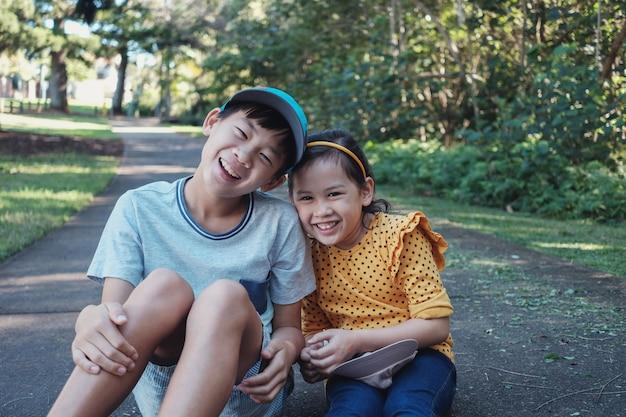 Mieszany azjatycki młodszy brat i siostra na zewnątrz,