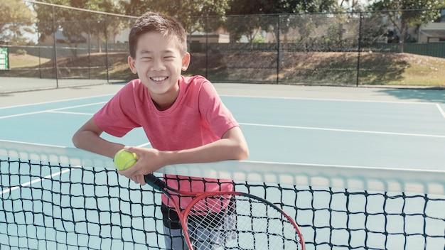 Mieszany azjatycki preteen chłopiec tween trzyma piłkę tenisową i rakietę, sport tween, aktywny tryb życia dzieciaka