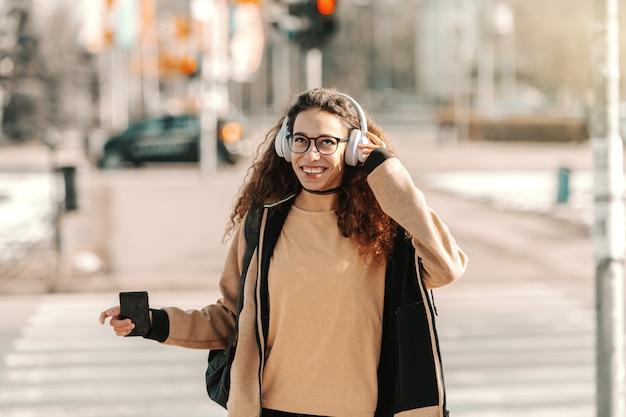 Mieszany biegowy nastoletni mieć hełmofony i słuchającą muzykę podczas gdy stojący na ulicie.