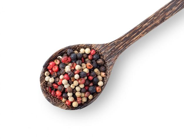 Mieszany pieprze gorący, czerwony, czarny, biały w drewnianej łyżce odizolowywającej na białym tle. widok z góry