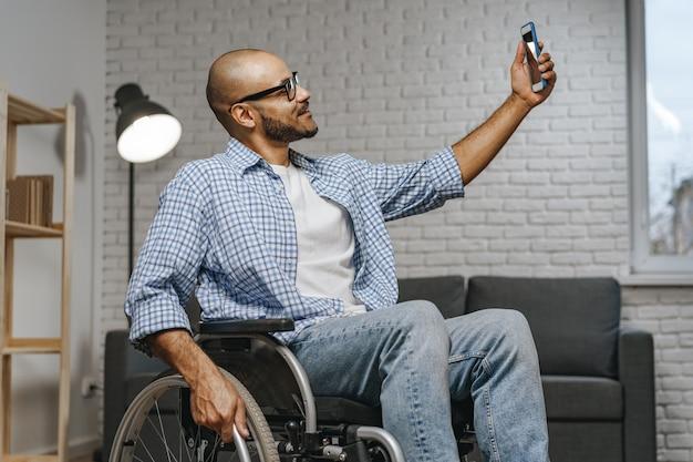 Mieszany ścigany niepełnosprawny mężczyzna siedzący na wózku inwalidzkim i korzystający ze smartfona