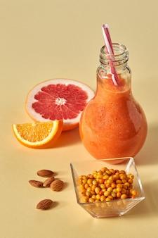 Mieszany sok cytrusowy z grejpfruta, pomarańczy, rokitnika i migdałów na żółtym tle papieru. witaminowy napój dietetyczny