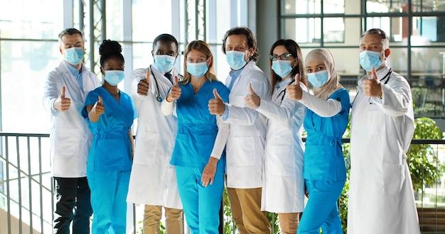 Mieszany zespół specjalistów, lekarzy płci męskiej i żeńskiej w szpitalu. międzynarodowa grupa medyków w maskach medycznych. chronieni pracownicy pokazujący kciuki do kamery. wieloetnicznych lekarzy i pielęgniarek