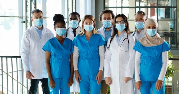 Mieszany zespół złożony z lekarzy płci męskiej i żeńskiej pozuje do kamery i krzyżuje ręce w szpitalu. międzynarodowa grupa medyków w maskach medycznych. chronieni wieloetniczni lekarze i pielęgniarki w przychodni