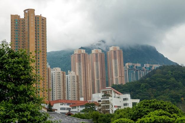 Mieszkalne wieżowce na tle zalesionych gór i niskich chmur
