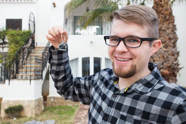 Mieszkanie, kupno domu, nieruchomości i koncepcja własności - przystojny mężczyzna pokazujący klucz do nowego domu.