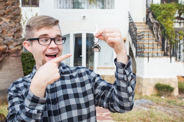 Mieszkanie kupno nieruchomości i koncepcji własności przystojny mężczyzna pokazujący klucz do nowego domu